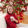 Blond smiling woman in front of Christmas tree — Stock Photo