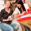 Two young woman wrapping Christmas present — Stock Photo