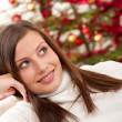 Smiling young woman in front of Christmas tree — Stock Photo