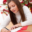 Young woman writing Christmas card — Stock Photo