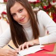 Young woman thinking while writing Christmas card — Stok fotoğraf