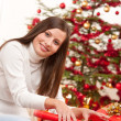 Stock Photo: Happy woman wrapping Christmas present