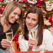Two young woman with champagne and Christmas tree — Stock Photo