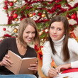 Two young women writing Christmas cards — Stock Photo #4695811