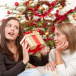 Two smiling women with Christmas present — Stock Photo
