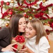 Two smiling women with Christmas present kissing — Stock Photo