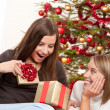 Two smiling women unpacking Christmas present — Stock Photo