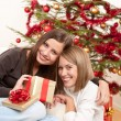 Two smiling women with Christmas present — Stock Photo #4695879