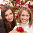 Two smiling women with Christmas present — Stock Photo #4695882