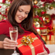 Smiling woman with Christmas present and glass of champagne — Stock Photo #4695964