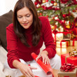 Young woman packing Christmas present — Stock Photo