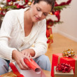 Stock Photo: Young woman packing Christmas present