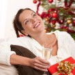 Smiling woman with Christmas present and glass of champagne — Stock Photo #4696021