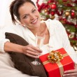 Smiling woman with Christmas present and glass of champagne — Stock Photo