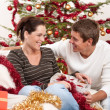 Young couple sitting together in front of Christmas tree — Stock Photo