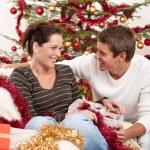 pareja de jóvenes sentados delante de árbol de Navidad — Foto de Stock