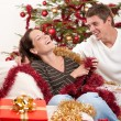 Photo: Young couple sitting together in front of Christmas tree