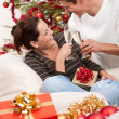 Young couple with champagne in front of Christmas tree — Stock Photo