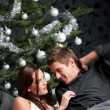 Extravagant man and woman in front of Christmas tree — 图库照片