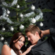 Extravagant man and woman in front of Christmas tree — Stock Photo