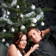 Extravagant man and woman in front of Christmas tree — Stockfoto