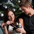 Young sexy couple in front of Christmas tree — Stock Photo