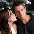 pareja joven sexy delante de árbol de Navidad — Foto de Stock