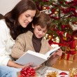 Stock Photo: Young mother with son reading book on Christmas