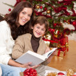 Young mother with son reading book on Christmas — Stockfoto