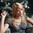 Foto Stock: Provocative woman posing in front of Christmas tree