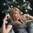 Provocative woman in gray dress in front of Christmas tree - Stock Photo
