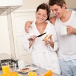 Happy couple having breakfast in the kitchen - Stock Photo