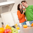 Royalty-Free Stock Photo: Young man and woman eating toast in the kitchen