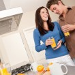 Young man and woman drinking orange juice — Stock Photo