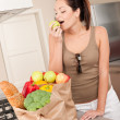 Young smiling woman with groceries in the kitchen — Stock Photo #4696245