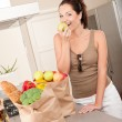 Young smiling woman with groceries in the kitchen — Stock Photo #4696246