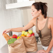 Stock Photo: Young womwith groceries in kitchen