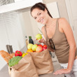 Royalty-Free Stock Photo: Young smiling woman with groceries in the kitchen