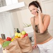 Young smiling woman with groceries in the kitchen — Stock Photo