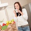 Young smiling womwith groceries in kitchen — Stockfoto #4696250