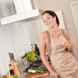Smiling young woman cooking in the kitchen — Photo
