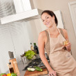 Smiling young woman cooking in the kitchen — Stockfoto