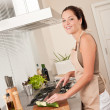 Young woman cutting zucchini in the kitchen — Stock Photo