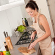 Smiling woman cutting bread in the kitchen — Stock Photo
