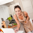 Woman with glass of white wine and laptop in the kitchen — Stock Photo