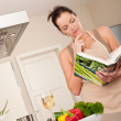 Royalty-Free Stock Photo: Young woman reading cookbook in the kitchen