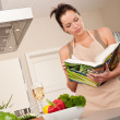 Young woman reading cookbook in the kitchen — Stock Photo #4696303