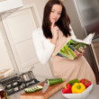 Stock Photo: Young woman reading cookbook in the kitchen