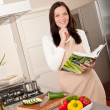 Smiling woman holding cookbook in the kitchen — Stock Photo