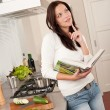 Beautiful woman holding cookbook in the kitchen — Stock Photo